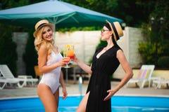 Lyckliga flickor med drycker på sommar festar nära pölen royaltyfri fotografi