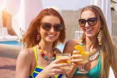 Lyckliga flickor med drycker på sommar festar nära pölen royaltyfria bilder