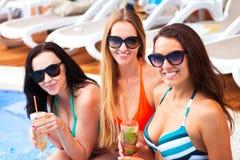 Lyckliga flickor med drycker på sommar festar nära pölen, sommar royaltyfria bilder
