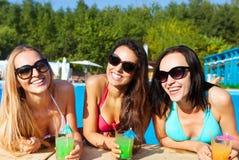 Lyckliga flickor med drycker på sommarpartiet royaltyfria bilder