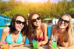Lyckliga flickor med drycker på sommarpartiet royaltyfri bild