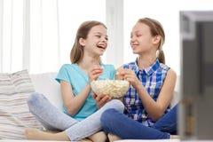 Lyckliga flickor med hållande ögonen på tv för popcorn hemma Arkivbild
