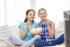Lyckliga flickor med hållande ögonen på tv för popcorn hemma Royaltyfri Bild