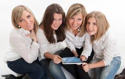 Lyckliga flickor med minnestavlaPC Royaltyfria Foton