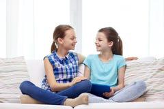 Lyckliga flickor med minnestavlaPC som hemma talar royaltyfri foto