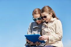Lyckliga flickor med minnestavlaPCdatoren utomhus Arkivbild