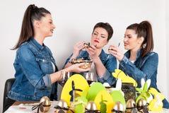 Lyckliga flickor med påskmålarfärgägg på det dekorerade ferieskrivbordet Arkivfoto