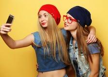 Lyckliga flickor med smartphonen över gul bakgrund Lycklig själv Royaltyfri Bild