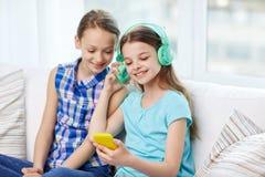 Lyckliga flickor med smartphonen och hörlurar Arkivfoto