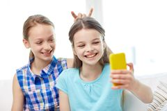 Lyckliga flickor med smartphonen som hemma tar selfie Arkivbild