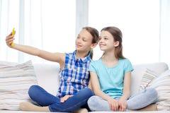 Lyckliga flickor med smartphonen som hemma tar selfie Royaltyfria Bilder