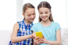 Lyckliga flickor med smartphonesammanträde på soffan Royaltyfria Foton