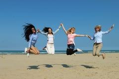 Lyckliga flickor på stranden som tillsammans hoppar Arkivfoto
