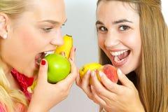 Lyckliga flickor som äter frukter Royaltyfria Bilder