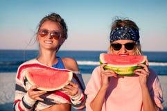 Lyckliga flickor som äter vattenmelon på stranden Kamratskap happines fotografering för bildbyråer