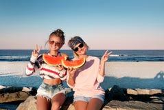 Lyckliga flickor som äter vattenmelon på stranden Kamratskap happines arkivbild