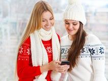 Lyckliga flickor som använder app på en mobiltelefon Royaltyfri Bild