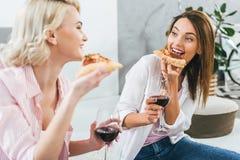 lyckliga flickor som dricker rött vin Arkivfoto