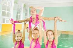 Lyckliga flickor som gör rutin i rytmisk gymnastik arkivfoto