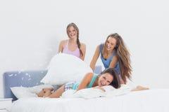 Lyckliga flickor som har gyckel på slummerpartiet i säng Fotografering för Bildbyråer