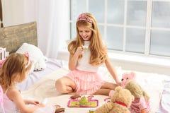Lyckliga flickor som har tebjudningen med dockor Arkivfoto