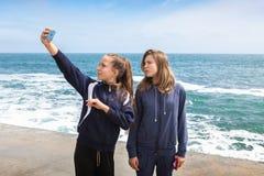 Lyckliga flickor som har tillsammans gyckel på stranden fotografering för bildbyråer