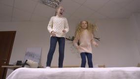 Lyckliga flickor som hoppar på säng stock video