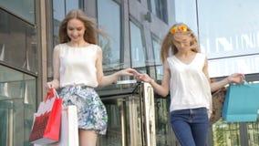 Lyckliga flickor som kommer ut ur lagret efter en stor försäljning stock video
