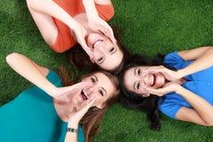 Lyckliga flickor som ligger på grönt gräs Arkivbilder