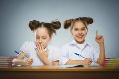 Lyckliga flickor som sitter på skrivbordet på grå bakgrund skola för copyspace för begrepp för svarta böcker för bakgrund royaltyfri foto