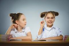 Lyckliga flickor som sitter på skrivbordet på grå bakgrund skola för copyspace för begrepp för svarta böcker för bakgrund arkivbild