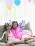 Lyckliga flickor som sitter på Sofa In Party Costumes Arkivbild