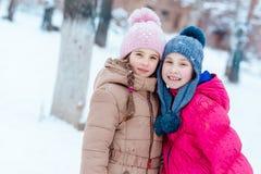 Lyckliga flickor som spelar på insnöad vinter Arkivfoton