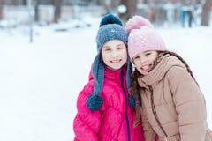 Lyckliga flickor som spelar på insnöad vinter Arkivbild