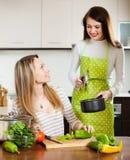 Lyckliga flickor som tillsammans lagar mat på inhemskt kök Royaltyfria Bilder