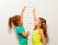 Lyckliga flickor sträcker händer upp på väggskala Fotografering för Bildbyråer