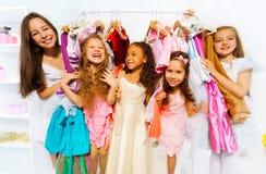 Lyckliga flickor under anseende bland klädhängare Royaltyfri Fotografi