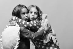 lyckliga flickor Ungar med roliga framsidor gör luftkyssar och rymmer kuddar Fotografering för Bildbyråer