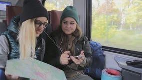 Lyckliga flickvänhandelsresande lyssnar till musik i drev arkivfilmer