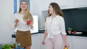 Lyckliga flickvänner med produkter i händer som dansar och skrattar under matlagning på bakgrundskök lager videofilmer