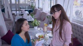 Lyckliga flickvänner som tillsammans tycker om lunch i hemtrevligt kafé och talar om sunt äta med anteckningsboken i hand stock video