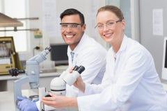 Lyckliga forskare som använder mikroskopet Arkivbild