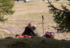 Lyckliga fotvandra par som tar ett avbrott på bergslinga i den Chocholowska dalen, Tatra, Arkivfoton