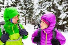Lyckliga fotvandrare för par som trekking i vinterträn royaltyfri fotografi
