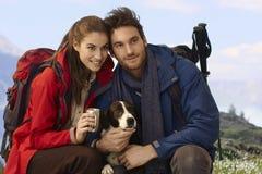 Lyckliga fotvandrare med hunden Arkivfoton