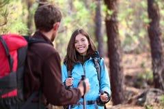Lyckliga fotvandrare som utomhus talar på skogvandring arkivfoto