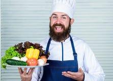 Lyckliga framl?gga utm?rkta gr?nsaker f?r man Nya sk?rdgr?nsaker Organisk mat Organiskt kulinariskt recept Ledar- kock arkivfoto