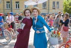 Lyckliga framsidor av två härliga kvinnor i gammalt mode klär med cykeln under Retro kryssning för utomhus- festival Fotografering för Bildbyråer