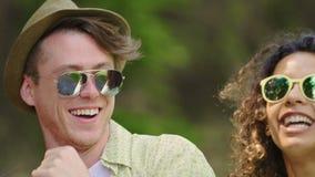 Lyckliga framsidor av ungt driftigt folk som dansar till musik på det frilufts- partiet, sommar stock video