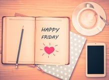 Lyckliga fredag på anteckningsboken, ilar blyertspennan, telefon- och kaffekoppen Arkivfoton